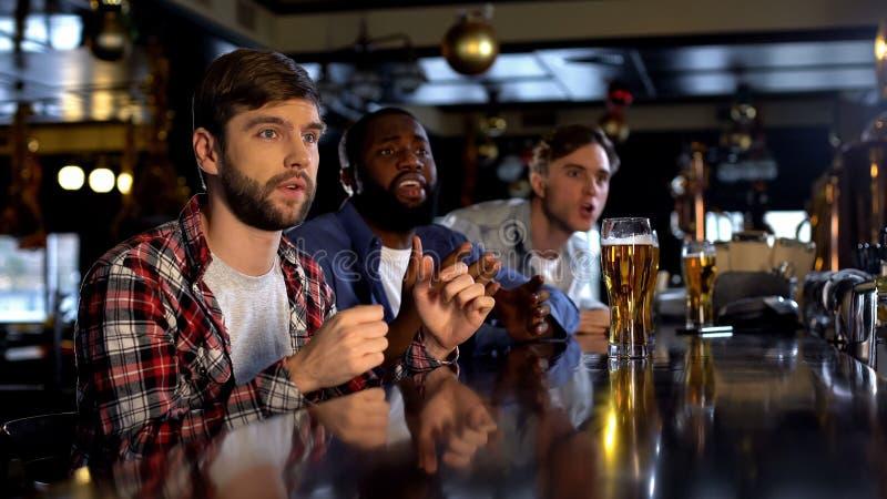 观看在酒吧的紧张的不同种族的人比赛,盼望队计分的目标 库存照片