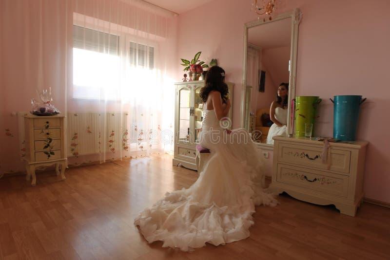 观看在镜子的新娘为她的婚礼做准备 免版税图库摄影