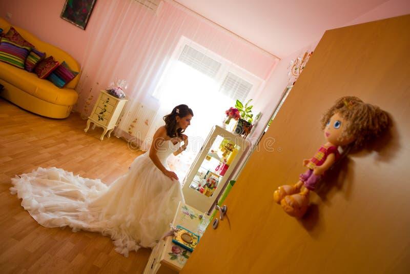 观看在镜子的新娘为她的婚礼做准备 库存照片