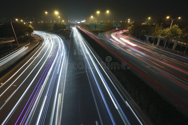 观看在高速公路的黄昏都市彩虹光夜交通 免版税库存图片