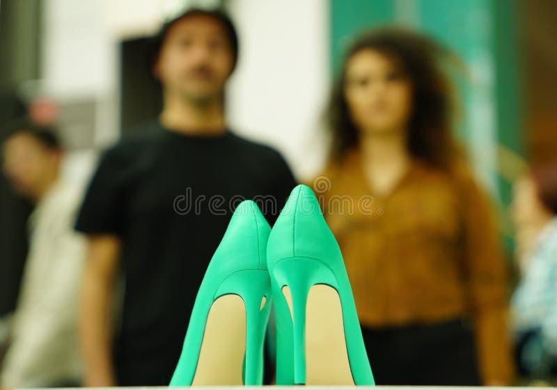 观看在vitrine的未认出的夫妇绿色妇女鞋子 库存照片