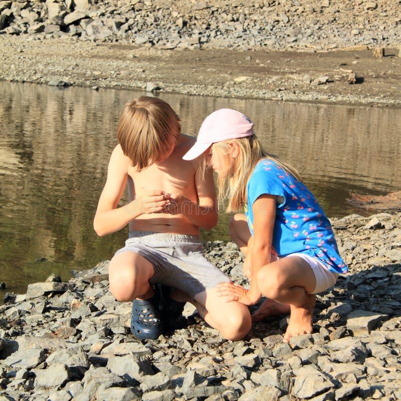 观看壳的孩子由湖 图库摄影