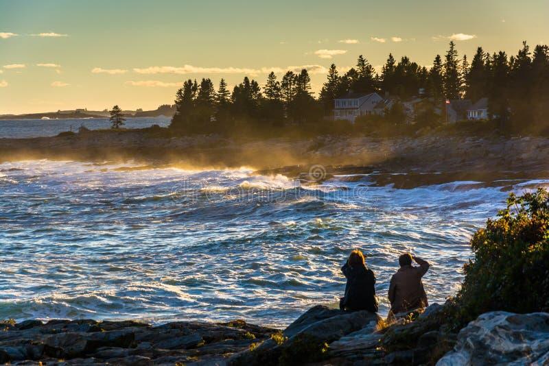 观看大波浪的夫妇在岩石碰撞在日落,在Pemaqui 免版税库存照片