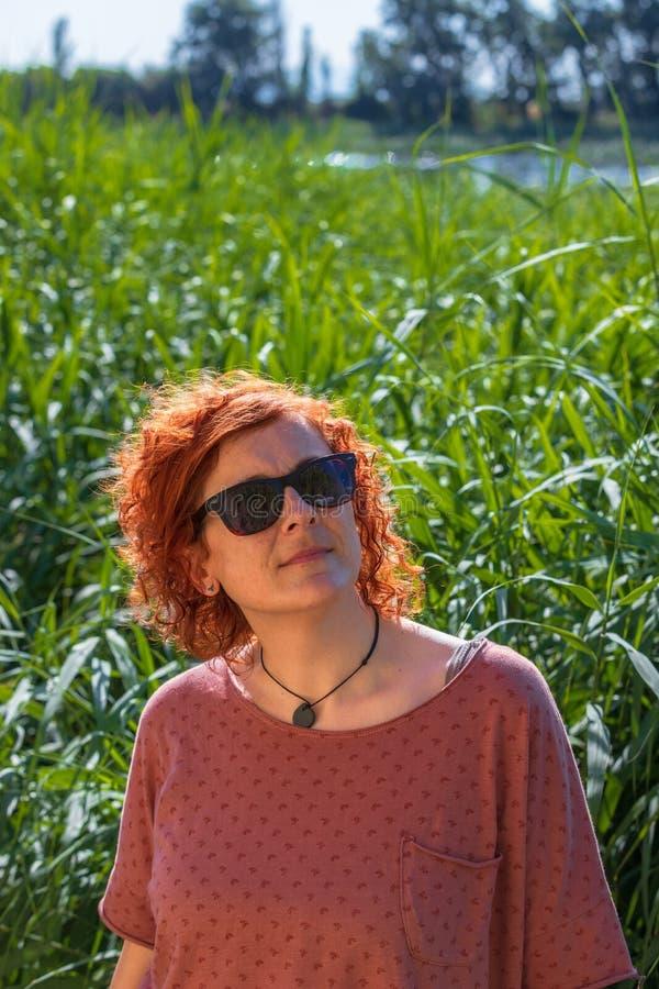 观看天空的妇女红头发人 免版税库存照片