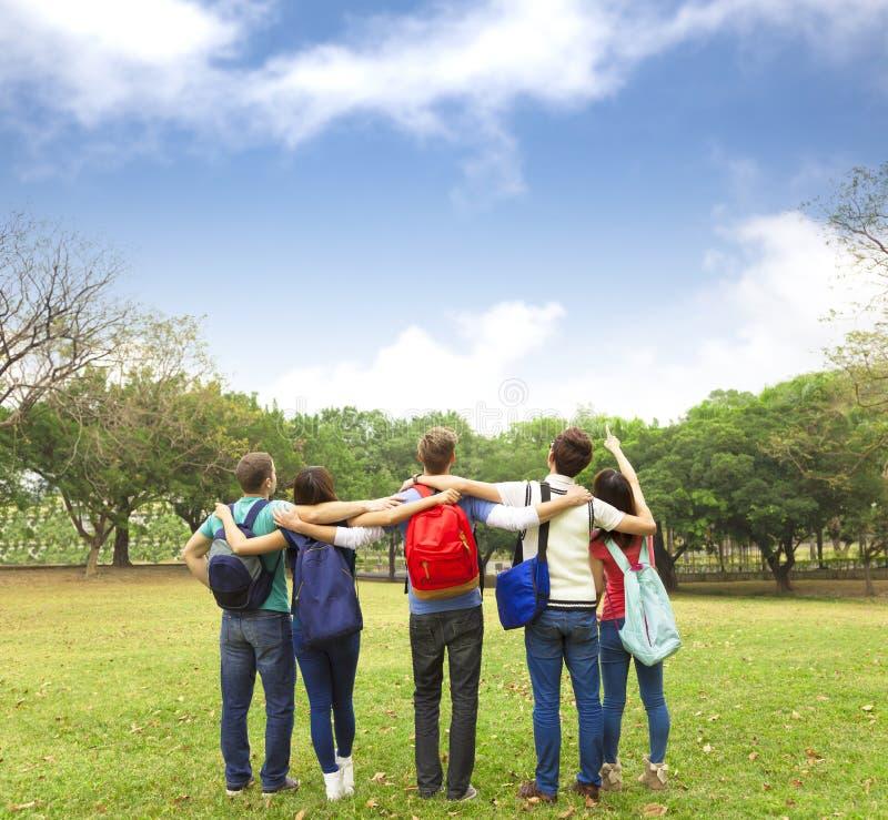 观看天空的年轻小组学生 库存图片