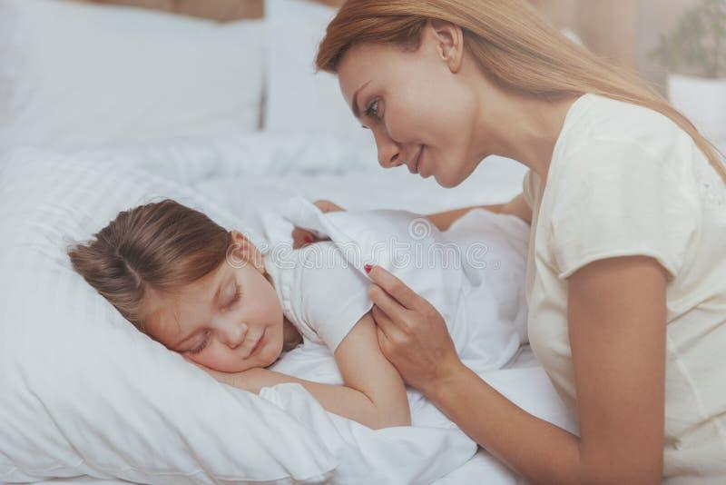 观看她女儿睡觉的可爱的妇女 免版税图库摄影