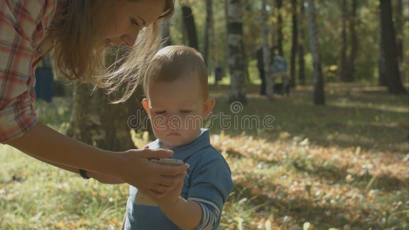 观看她的儿子的母亲特写镜头画象谈在手机 图库摄影