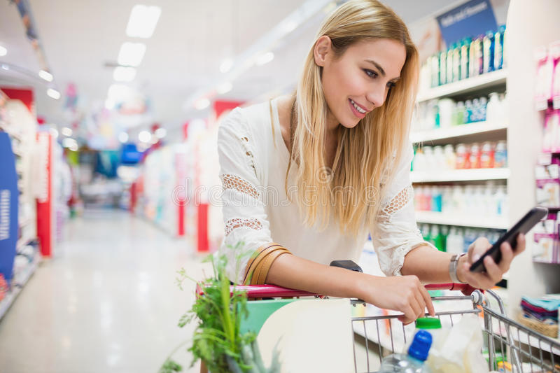 观看她的电话的微笑的顾客在超级市场 免版税图库摄影