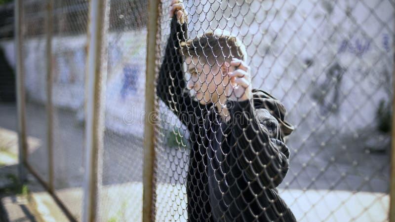观看富有的区的白种人男孩通过篱芭,贫穷,移民 免版税图库摄影