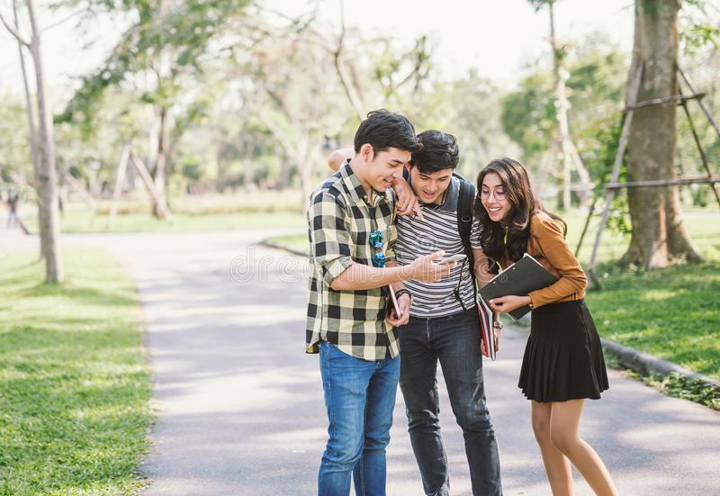 观看巧妙的电话的小组快乐的朋友室外 库存图片
