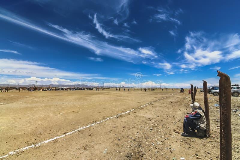 观看当地人的观众踢在一个无油气地区的橄榄球足球 库存照片