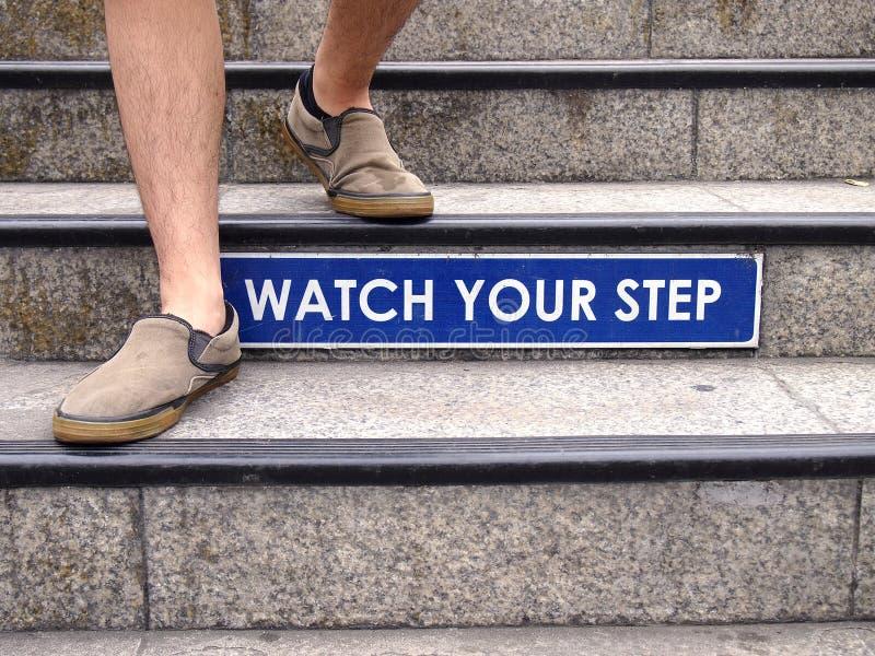 观看您的在楼梯的步标志和一个对脚 免版税库存照片