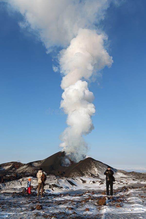 观看扎尔巴奇克火山火山的爆发的游人,抛出熔岩、蒸汽、气体和灰 堪察加 库存图片