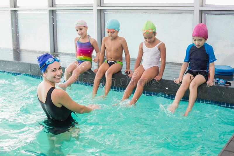 观看教练的逗人喜爱的游泳类 免版税库存图片