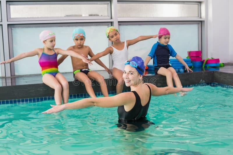 观看教练的逗人喜爱的游泳类 免版税图库摄影