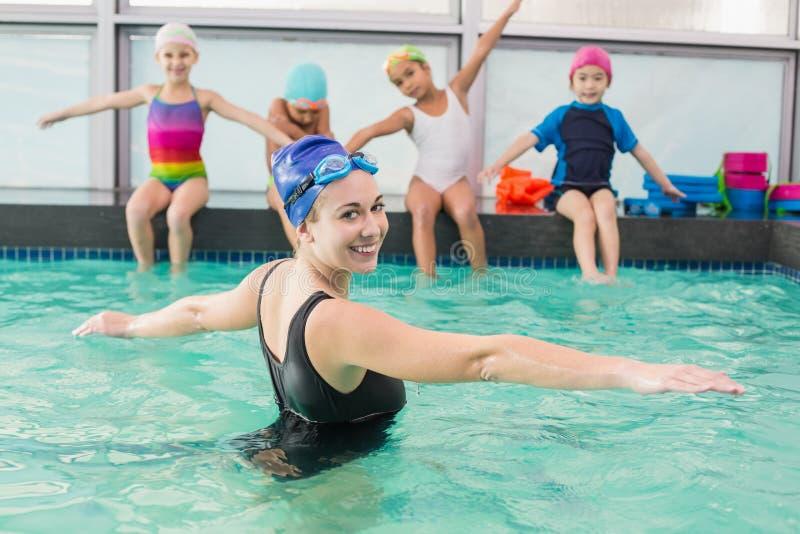 观看教练的逗人喜爱的游泳类 免版税库存照片