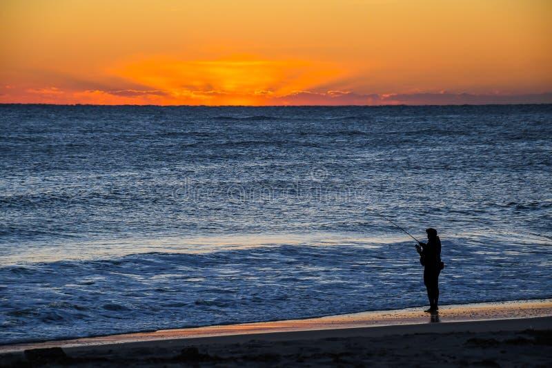 观看日出的海浪渔夫 免版税库存图片