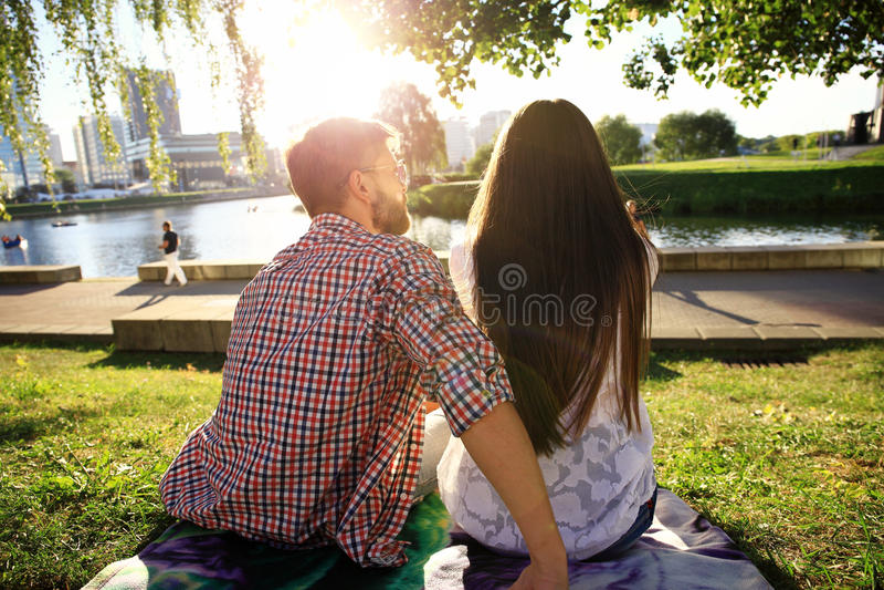 观看日落的爱恋的夫妇画象  免版税库存图片