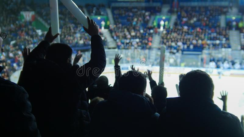 观看曲棍球比赛的一个小组年轻人 热烈的欢迎 库存照片