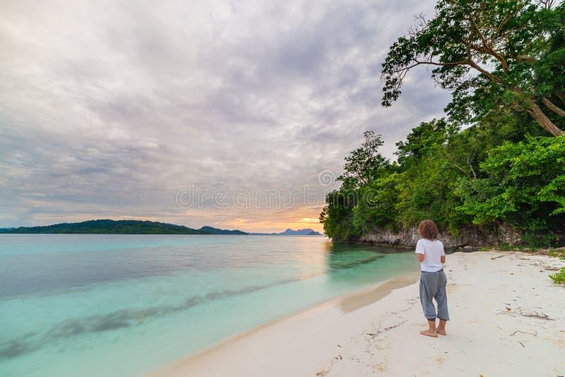 观看松弛日落的游人坐海滩在遥远的Togean海岛,中央苏拉威西岛,印度尼西亚, upgrowing的trave 免版税库存图片
