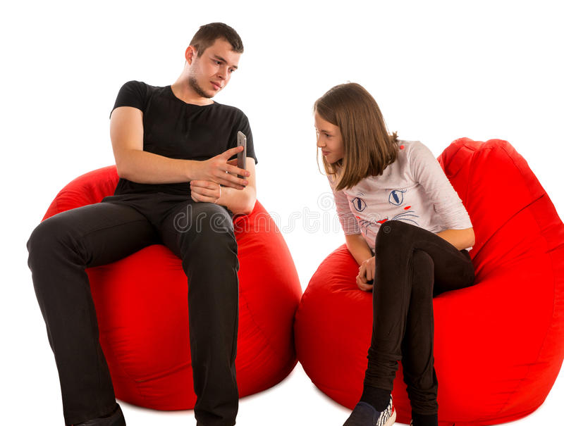 年轻观看某事在电话的人和女孩,当坐时 免版税库存照片