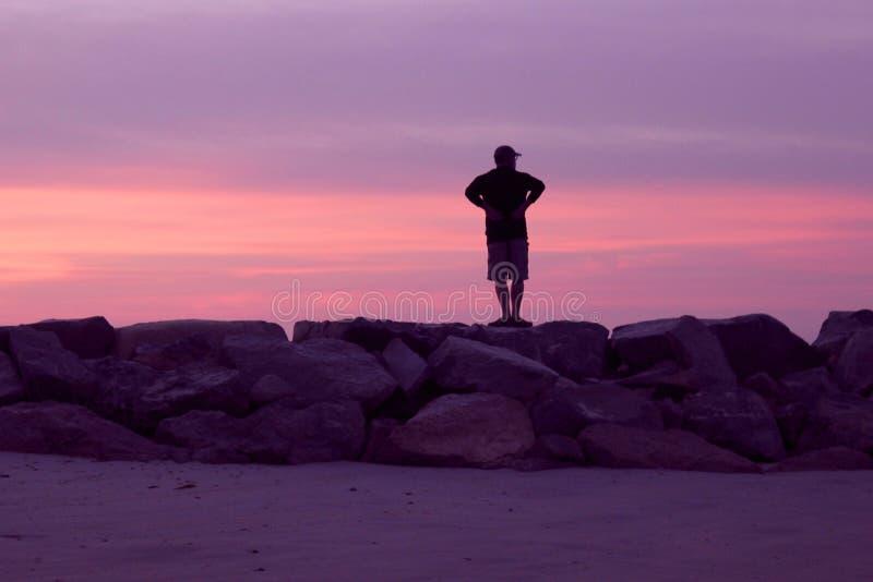 观看桃红色和紫罗兰色日落的人在海滩 库存图片