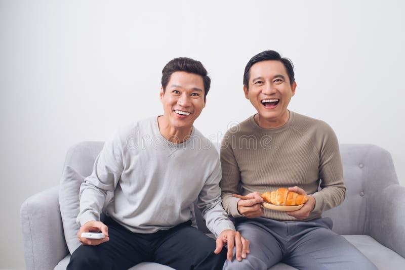 观看橄榄球的两个男性朋友在家坐沙发 免版税库存图片