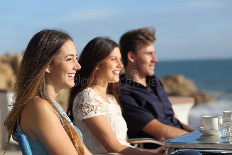 观看海滩的三个愉快的朋友在咖啡馆 免版税库存照片
