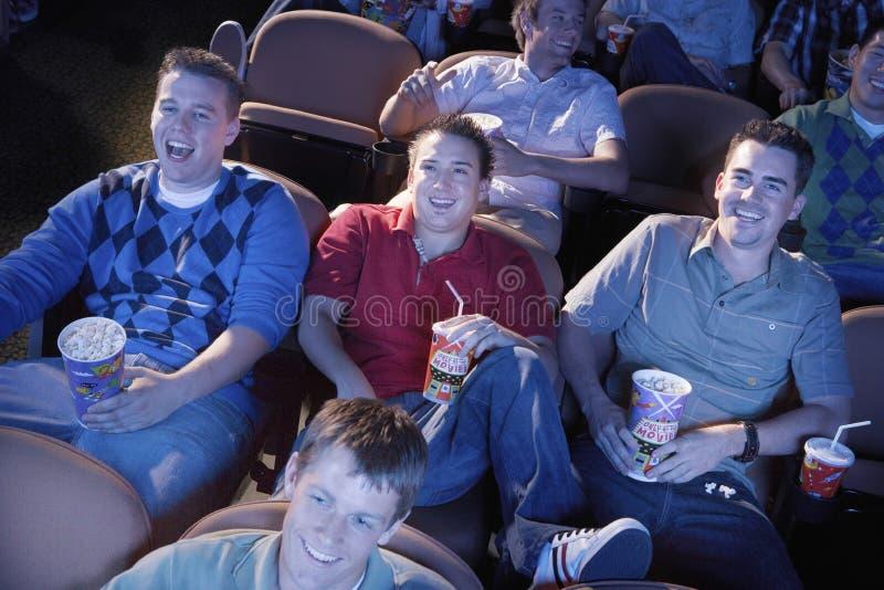 观看电影的男性朋友在剧院 库存照片