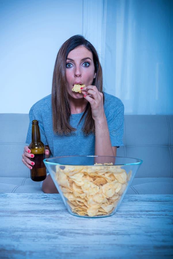 观看电视和吃的热情的妇女 库存图片