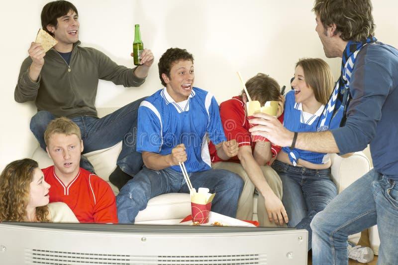 观看电视和庆祝的朋友 免版税图库摄影