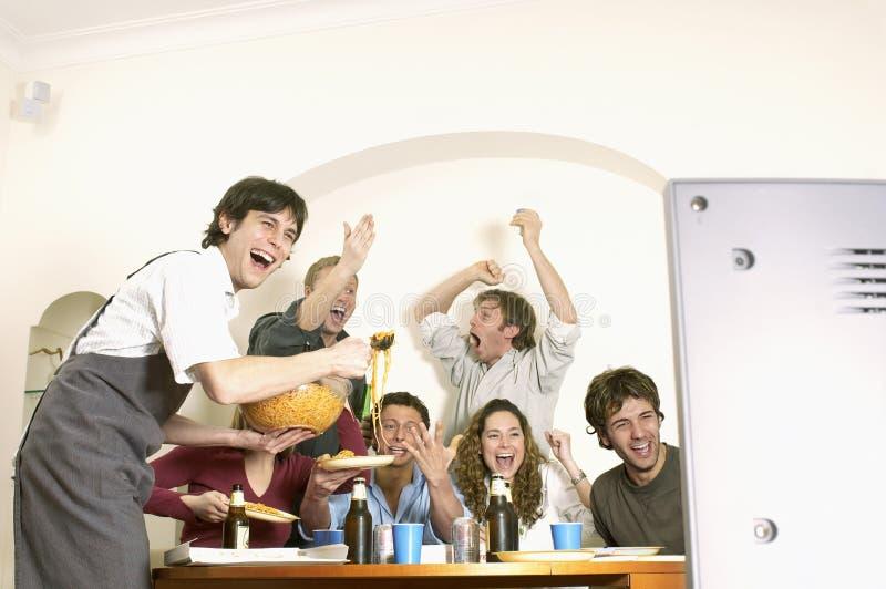 观看电视和庆祝的朋友 免版税库存照片