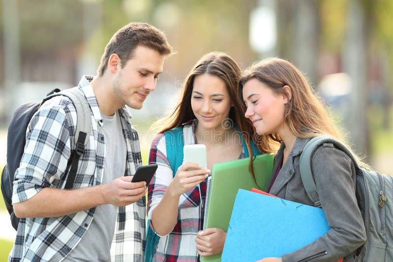 观看电话内容外部的轻松的学生 免版税库存照片