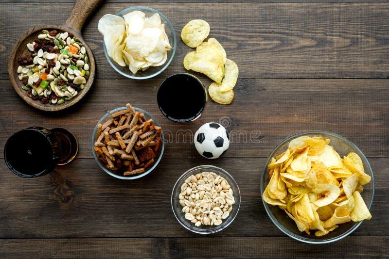 观看的橄榄球的快餐在电视 体育运动注意 芯片、坚果、面包干淡啤酒和足球在黑暗木 免版税图库摄影