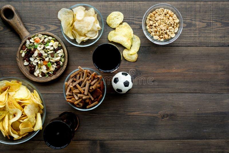 观看的橄榄球的快餐在电视 体育运动注意 芯片、坚果、面包干淡啤酒和足球在黑暗木 免版税库存图片