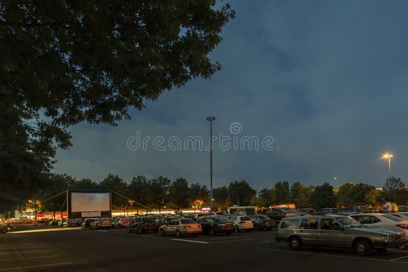 观看的电影户外从在城市停车场的汽车 库存照片