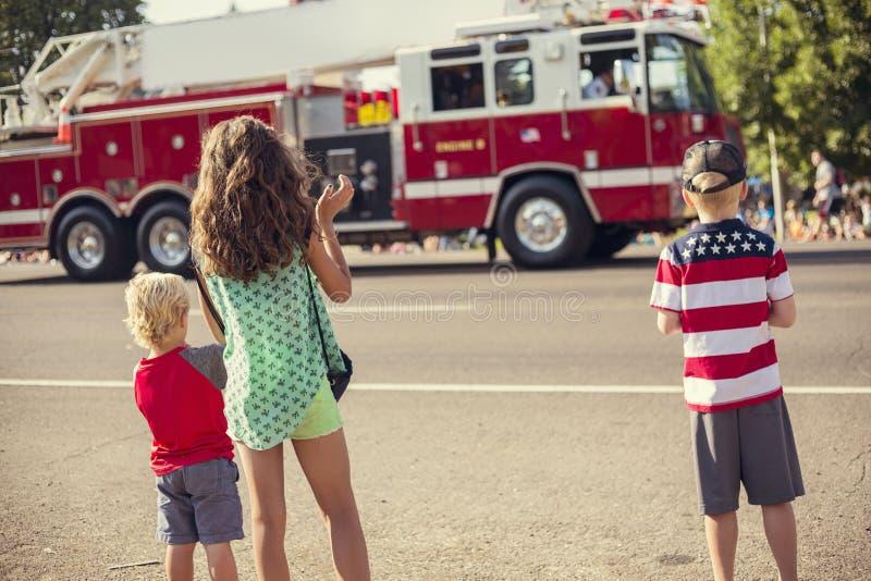 观看美国独立日游行的孩子 免版税库存图片