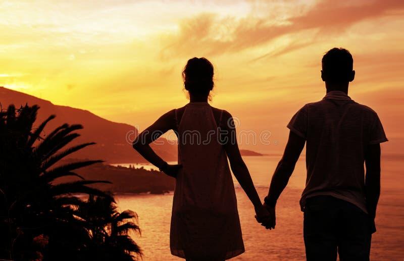 观看美好,热带日落的快乐的夫妇 免版税库存图片