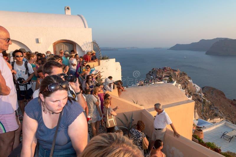 观看著名Santorinian日落的人人群  免版税库存照片