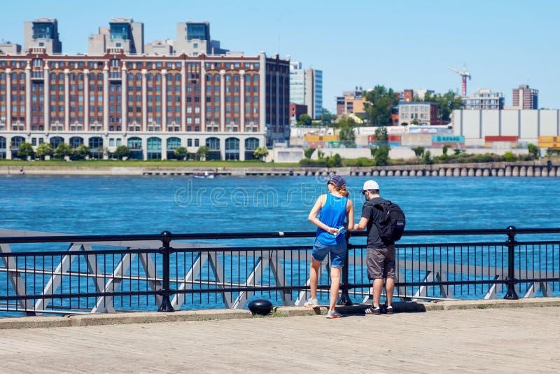 观看蒙特利尔市和圣劳伦斯河的风景年轻嬉戏夫妇在一个晴朗的夏日在魁北克,加拿大 免版税库存照片