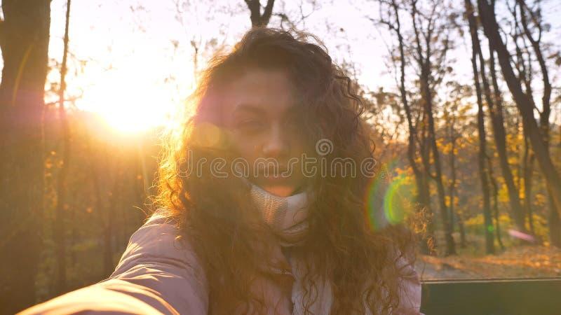 观看认真地入照相机的卷发的白种人女孩Selfie照片在晴朗的秋季公园 图库摄影