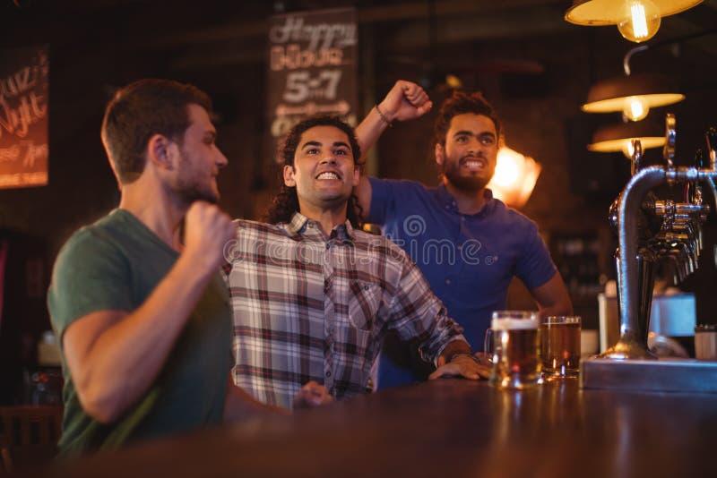 观看足球比赛的小组男性朋友 免版税库存图片