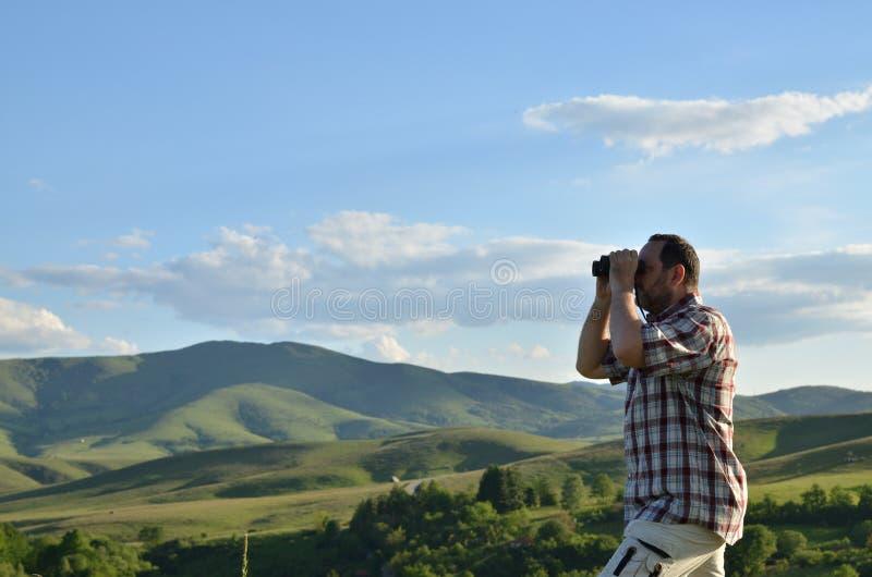 观看风景风景的人通过双筒望远镜 免版税图库摄影