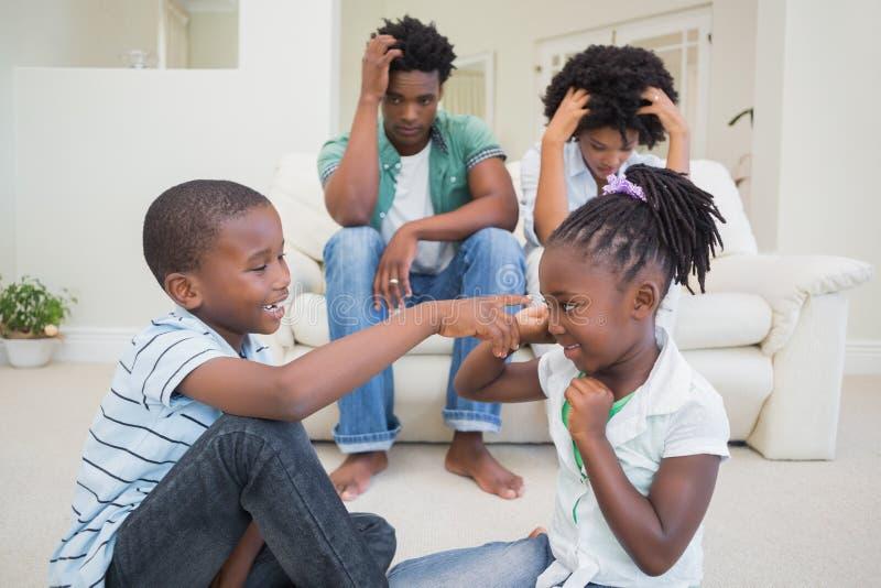 观看他们的儿童战斗的沮丧的父母 图库摄影