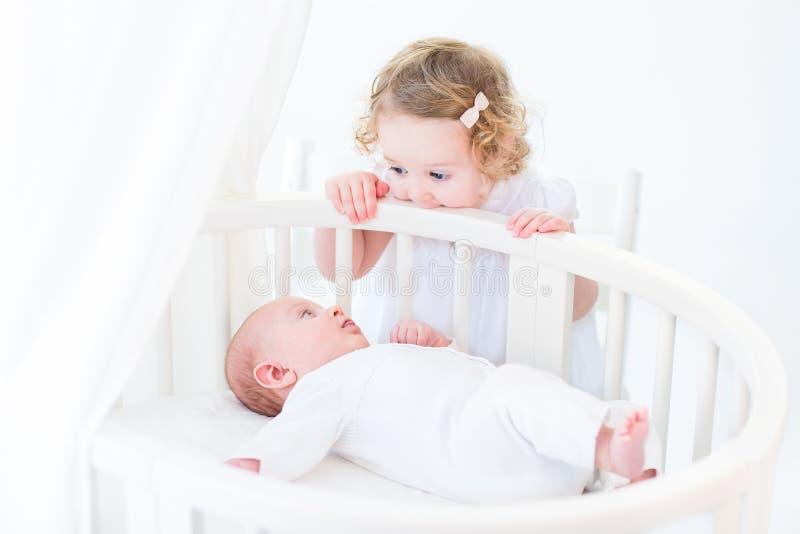 观看他的小孩姐妹的逗人喜爱的新出生的男婴站立在喂 免版税库存照片