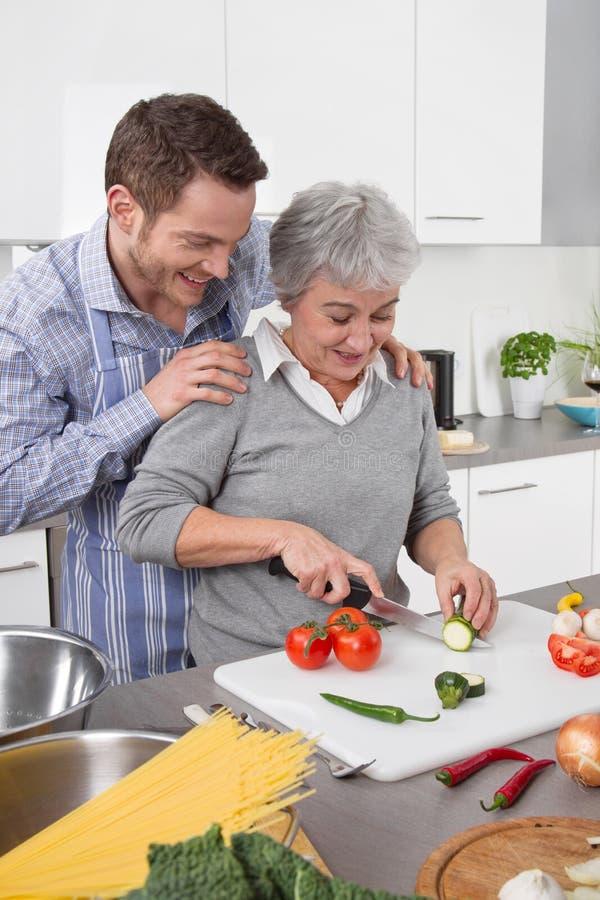 观看他的母亲的人在厨房烹调 免版税库存图片