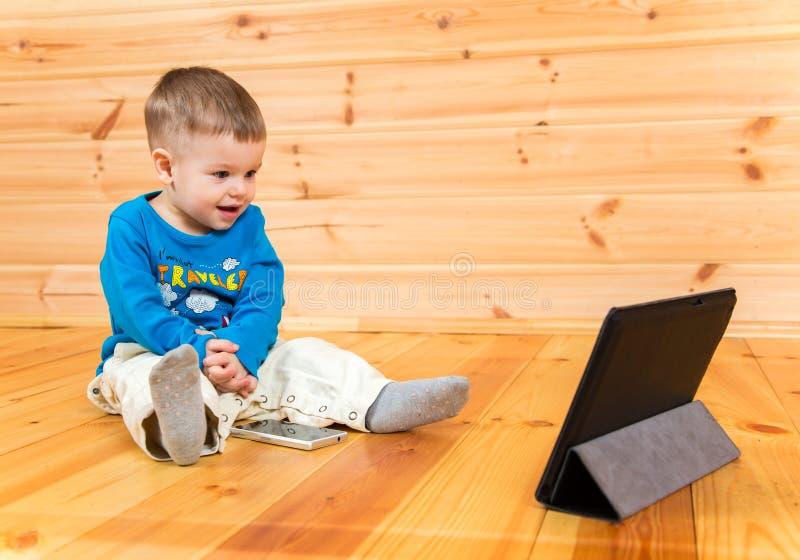 观看他的片剂计算机的激动的男婴 免版税库存照片