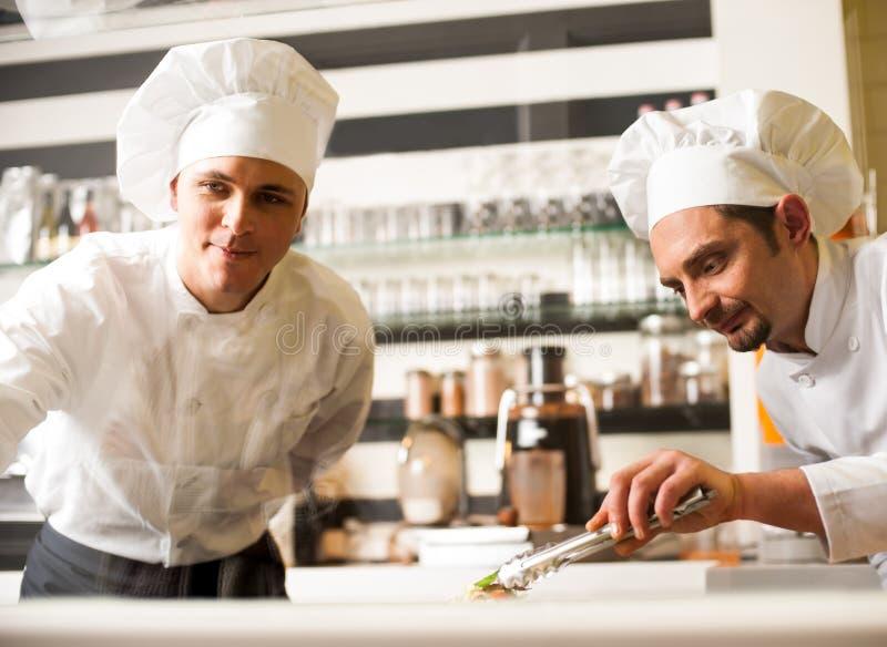 观看他的辅助安排的盘的厨师 免版税图库摄影