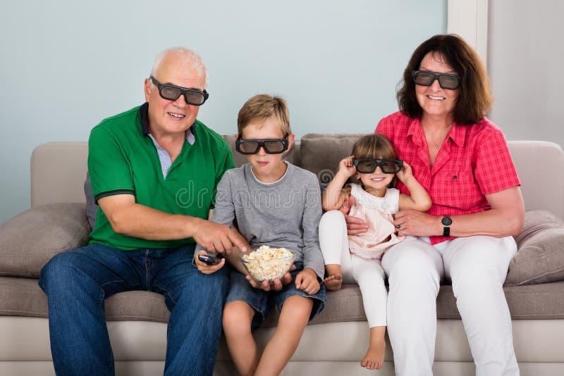 观看3D电影的祖父母和孙 免版税库存照片
