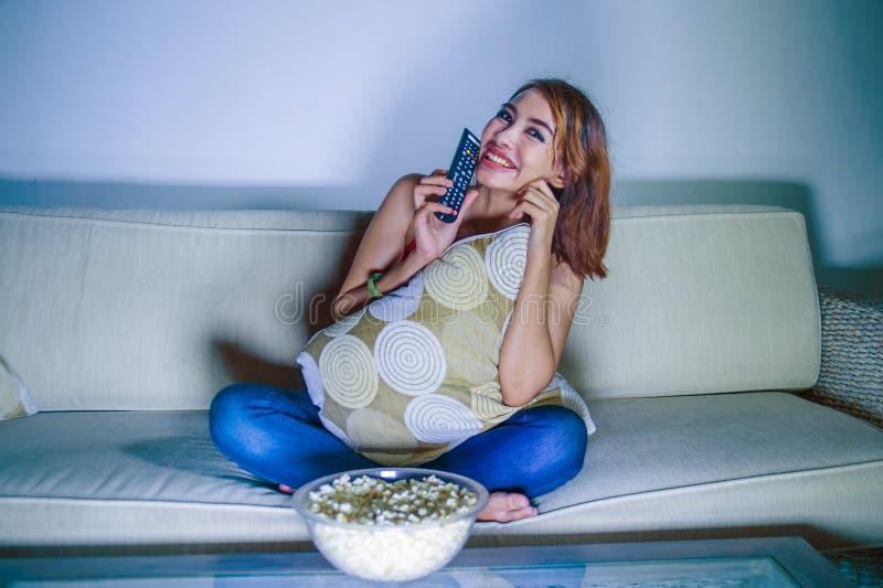 观看tel的年轻愉快的西班牙拉丁妇女在家沙发长沙发 免版税库存照片
